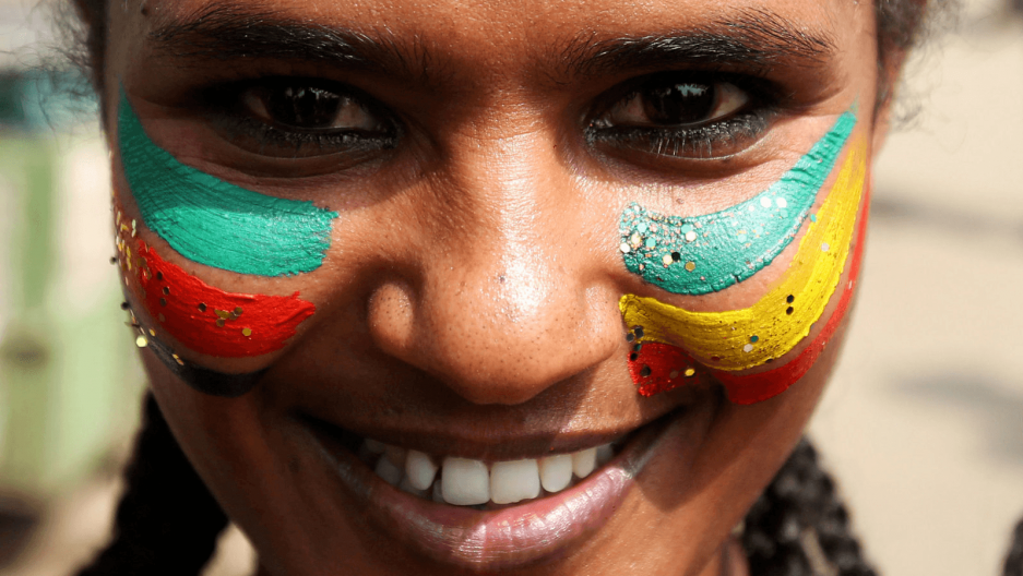 a woman's face painted with ethiopian and eritrean flags