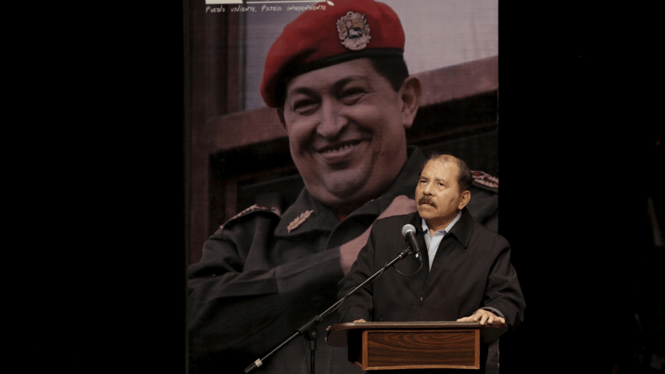 Daniel Ortega speaks in front of a huge picture of Hugo Chavez