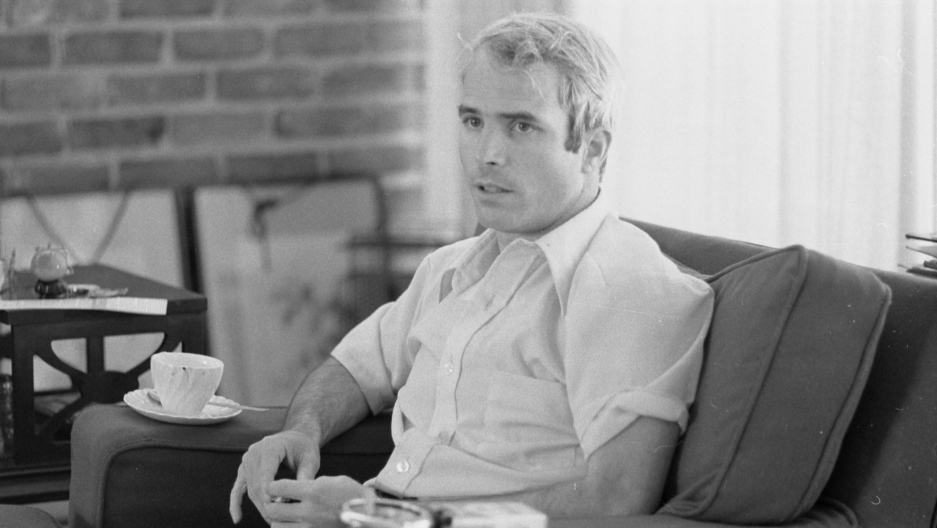 John McCain is shown in a blakc and white photographer in 1973, being interviewed about his experiences as a prisoner of war during the war in Vietnam.