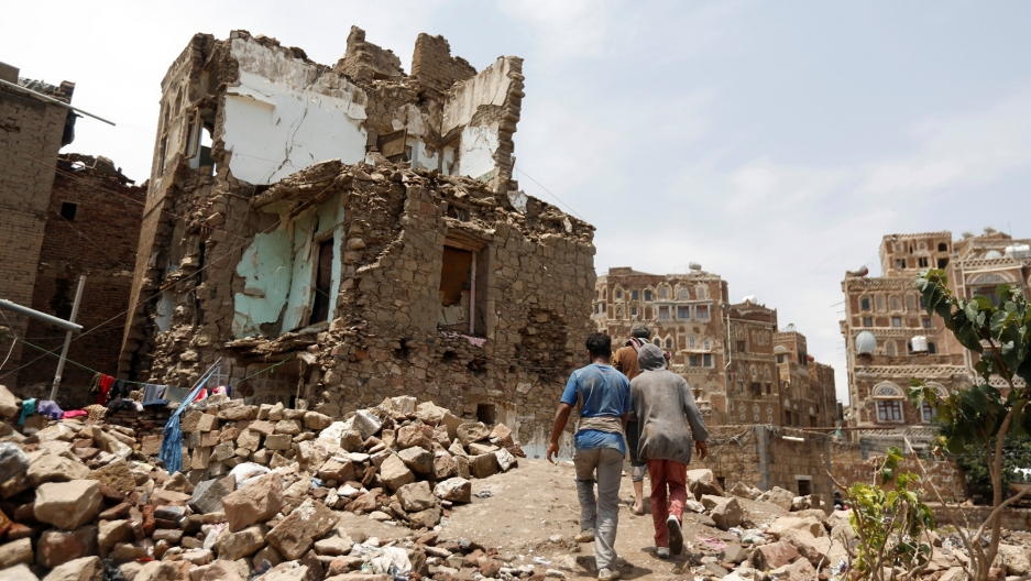 Three people walk past a stone house bombed out by an air strike in the old quarter of Sanaa, Yemen, August 8, 2018.
