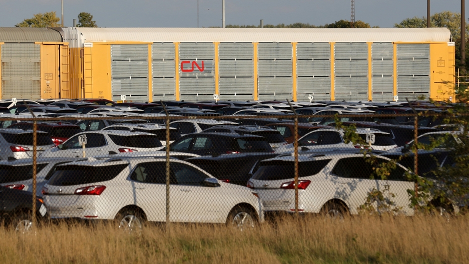 Chevrolet Equinox SUVs are shown parked in a fenced in area with CN Rail cars in tbe background.