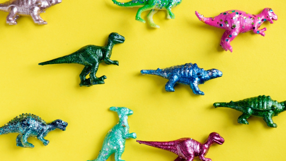 toy dinosaurs on a yellow background