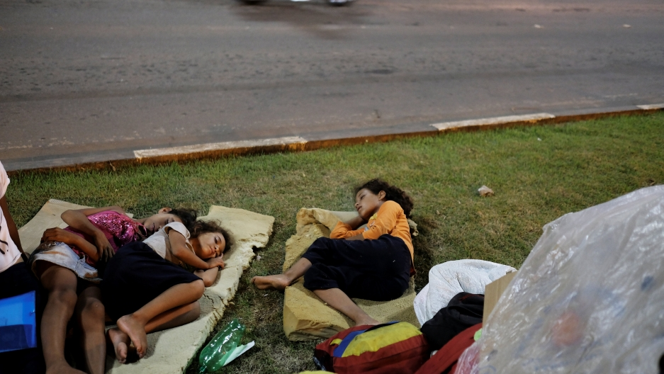 Venezuelan children sleep on the grass