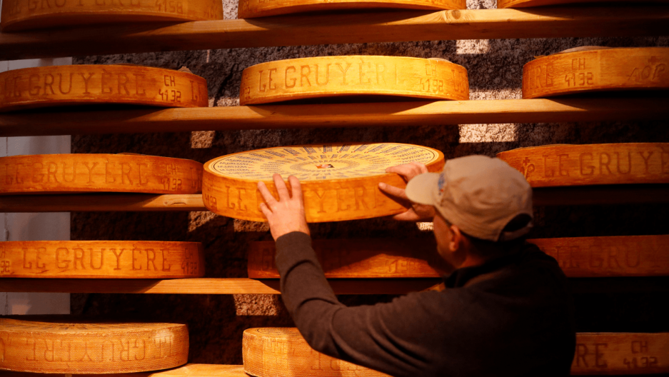 a man stands in front of a wall full of wheels of cheese