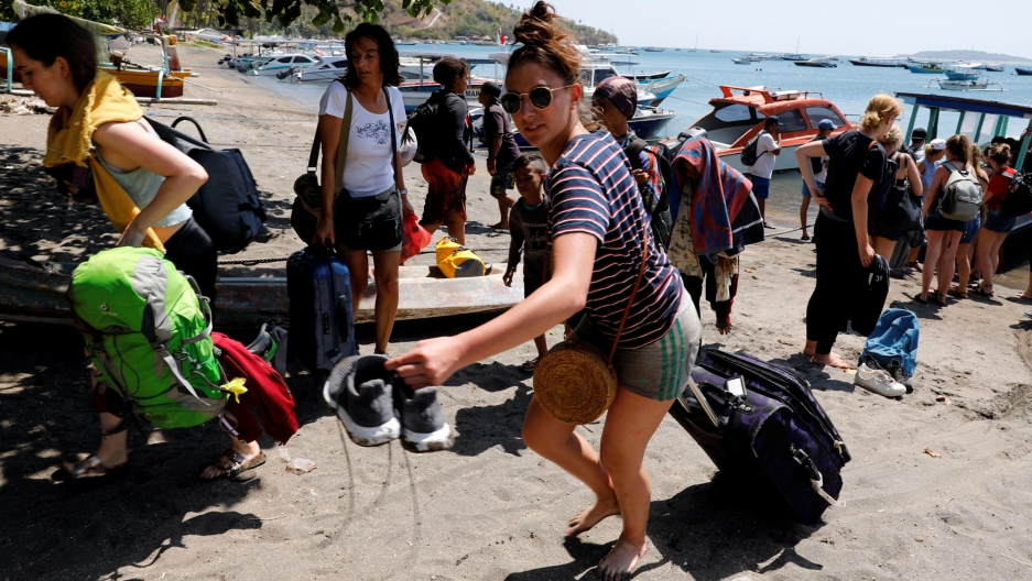 Foreign tourists carry their backpacks and rollaboards across the sandy beach after an earthquake hit Lombok island in Indonesia August 6, 2018.