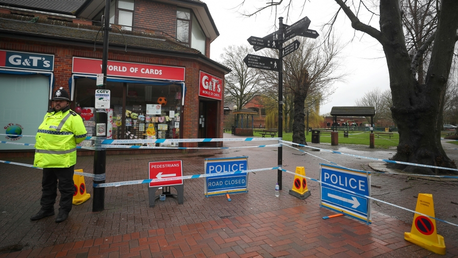 A police officer is shown standing to the left of the photograph, wearing a fluorescent jacket guards a cordoned off area where former Russian intelligence officer Sergei Skripal and his daughter Yulia were found poisoned.
