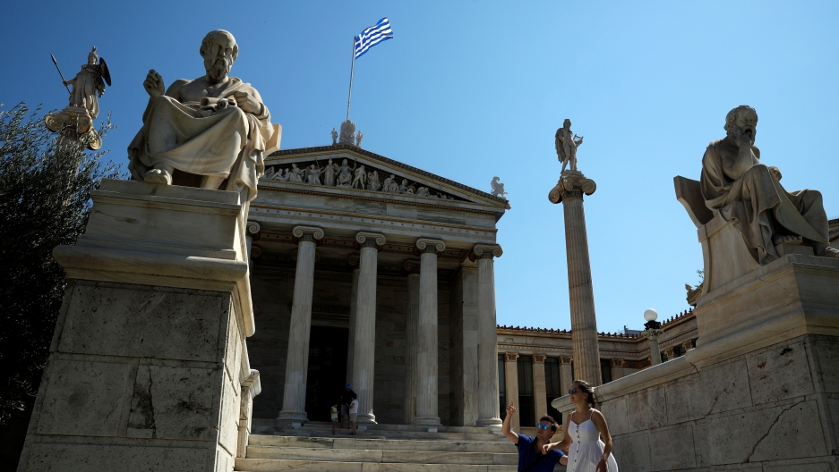 the front steps of front of the Athens Academy in Athens, Greece,