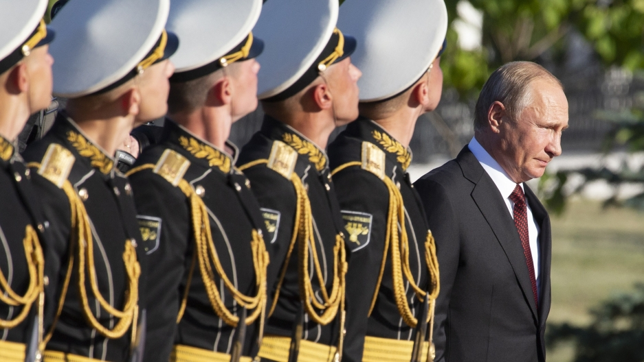 Putin with a line of soldiers behind him in uniform