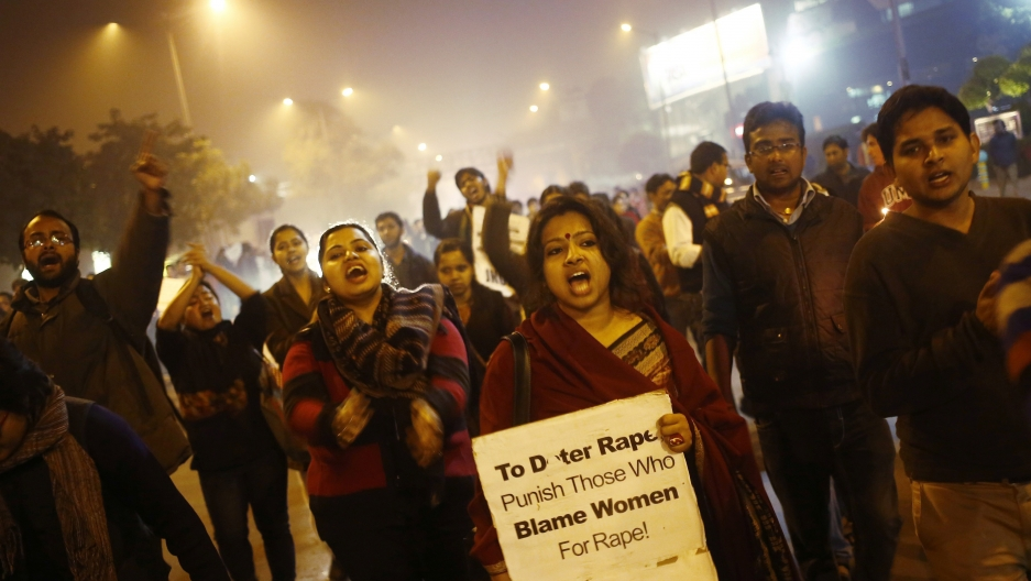 Demonstrators shout slogans during a candlelight vigil in Delhi
