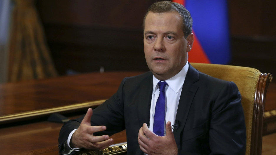 Russian Prime Minister Dmitry Medvedev is shown sitting in a chair with yellow fabric, speaking during an interview outside Moscow.
