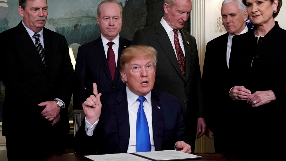 President Donald Trump, surrounded by business leaders and administration officials, prepares to sign a memorandum on intellectual property tariffs on high-tech goods from China, at the White House in Washington, March 22, 2018.