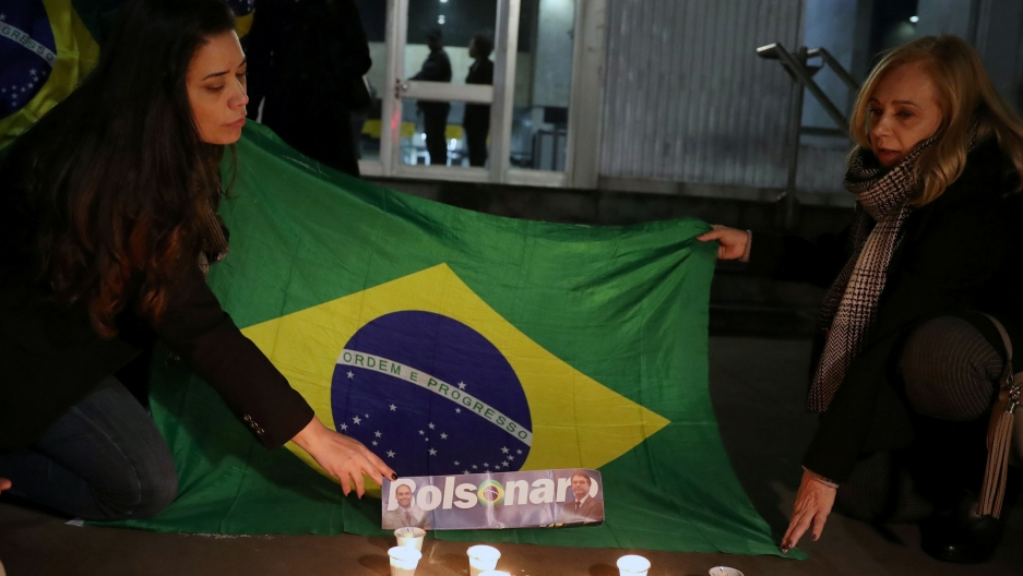 Two women kneel next to a Brazilian flag as they light candles