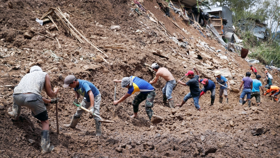 A row of men with shovels stand on a hillside covered in debris and loose mud after a mudslide covered a mining town
