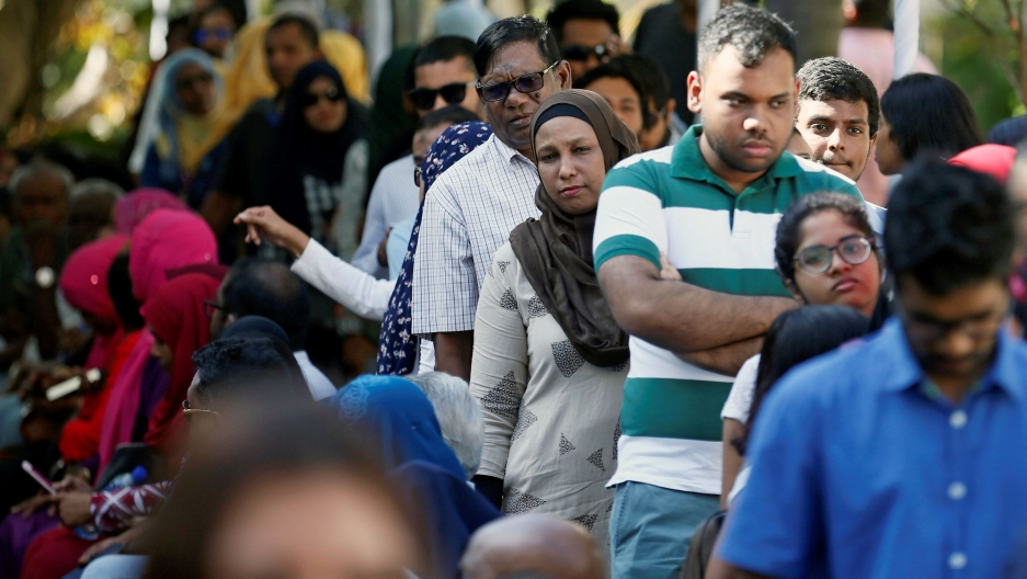 A crowd of people fill a street waiting on line to vote in Sri Lanka