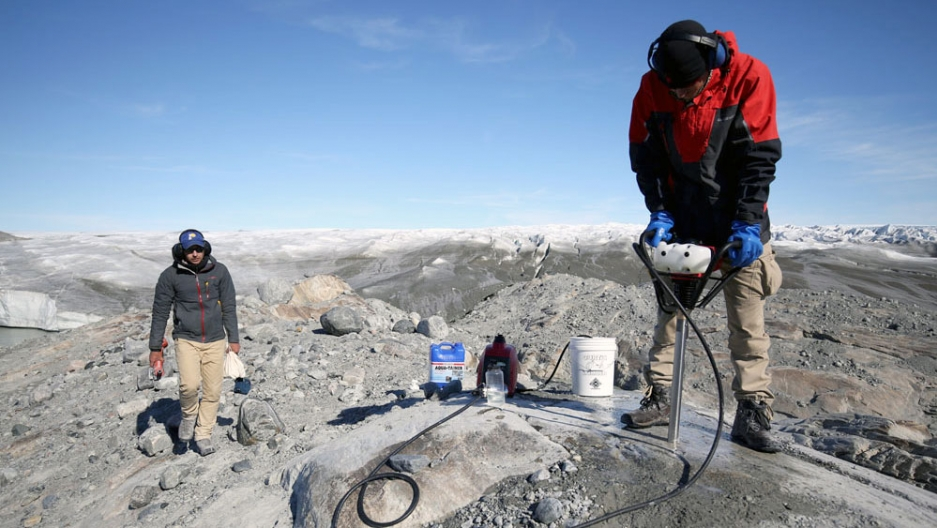 Two men stand on rocky land as mountains and snow stretch out behind them. One holds a drill of some kind and is drilling into the rock.
