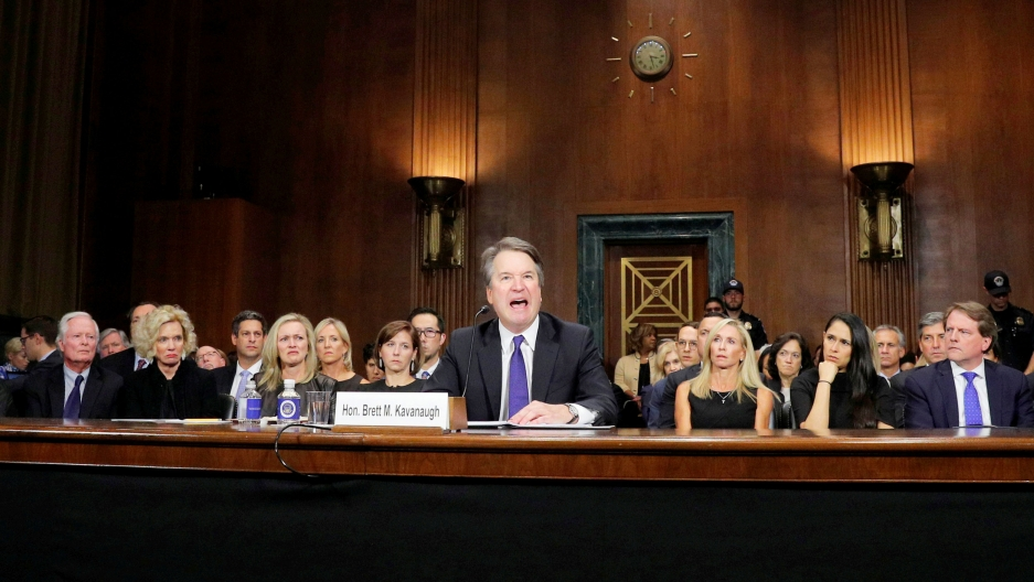 Brett Kavaugh is pictured at a table in the US Capitol. A row of women are behind him.