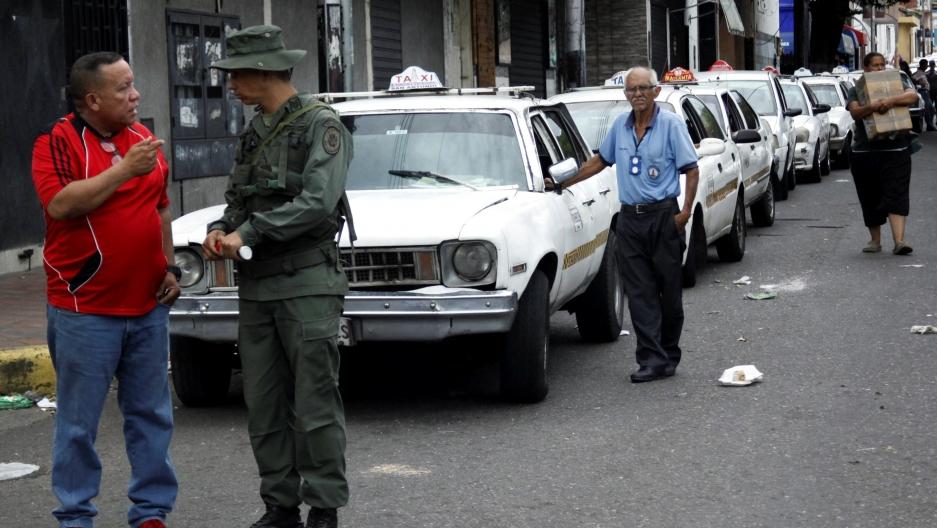 A Venezuelan soldier speaks with a man
