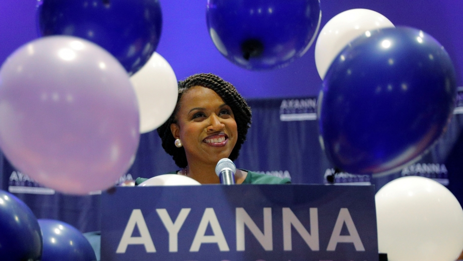 Balloons fall around Democratic candidate for the US House of Representatives Ayanna Pressley as she stands behind a podium smiling.