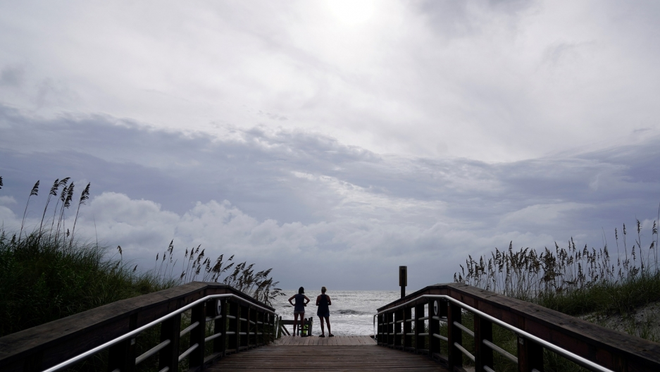 People look out over the surf at the end of a long wooden walkway with the ocean and large clouds off in the distance.