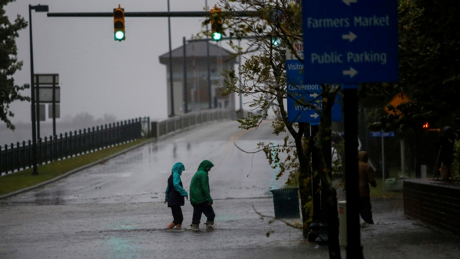 People are shown in rain jackets wading through a flooded street in New Bern, North Carolina, Sept. 13, 2018.