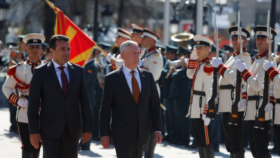 Macedonian Prime Minister Zoran Zaev and US Secretary of Defense James Mattis are shown walking past military officials in dress uniforms during a welcoming ceremony in Skopje.