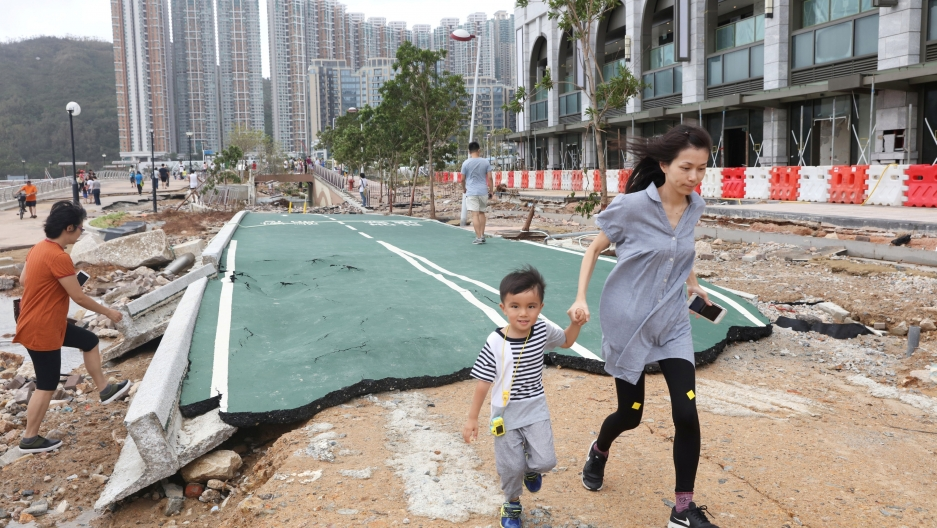 A boy and his mother walk through rubble