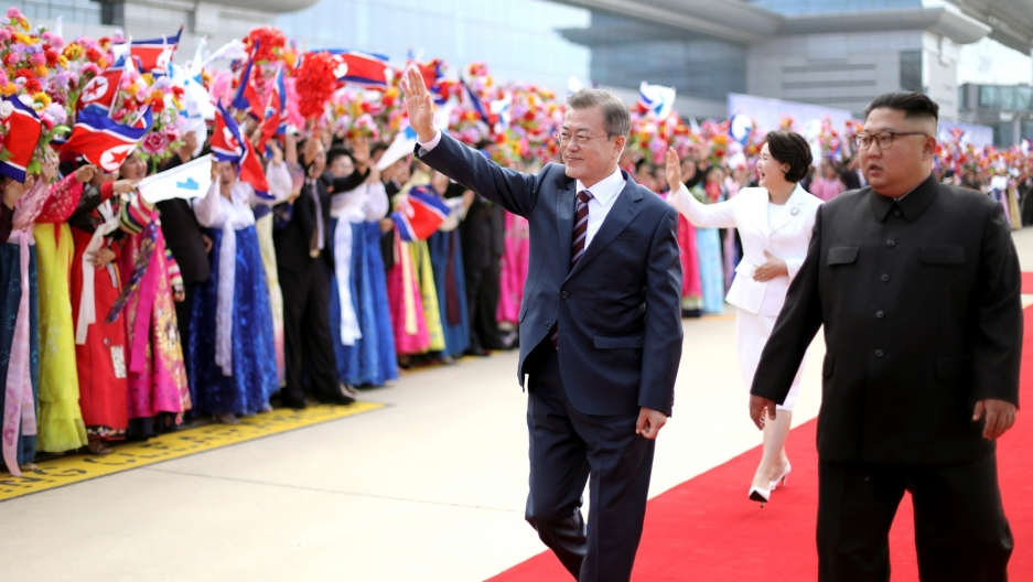 South Korean President Moon Jae-in and North Korean leader Kim Jong-un walk past a welcoming crowd in traditional Korean dress waving flowers and North Korean flags.