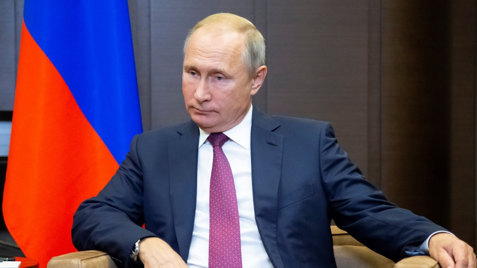 Russian President Vladimir Putin is shown with a Russian flag behind him looking off to his right at a meeting in Sochi, Russia.