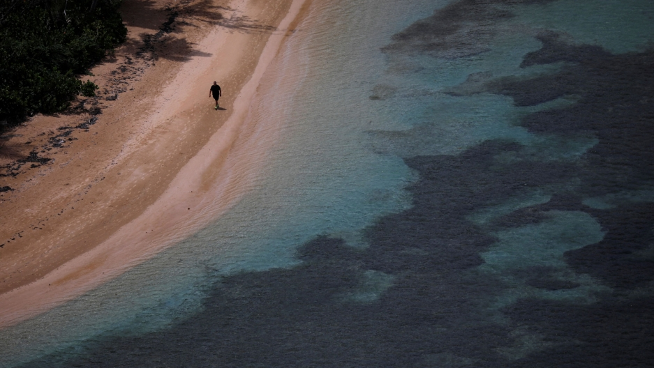 A man walks along an empty beach light and dark blue waters near Ceiba, Puerto Rico, Sept. 18, 2018.