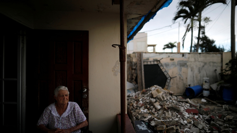Lucila Cabrera is shown sitting on her porch with damaged buildings visible nearby.
