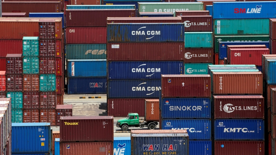 Shipping containers are seen at a port in Shanghai, China, with a green truck driving through the middle.