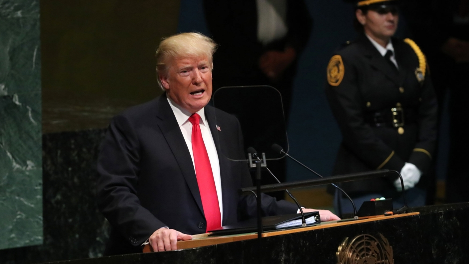 US President Donald Trump, in a red tie and dark suit, is shown at podium addressing the United Nations General Assembly.