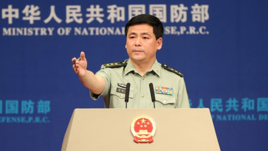 Chinese Defense Ministry spokesman Ren Guoqiang is shown at a podium with his arm outstretched.