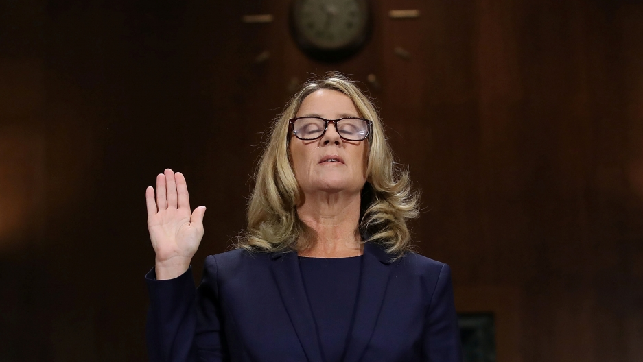 Dr. Christine Blasey Ford is shown with her right hand raised and eyes closed.