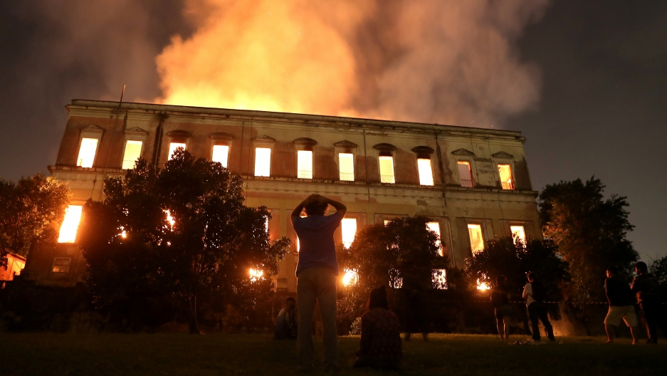 People watch as a fire burns at the National Museum of Brazil