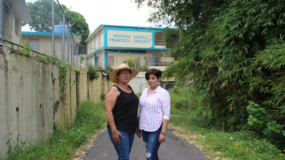 Two women in front of school