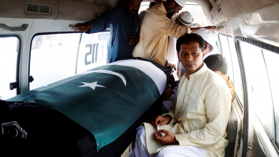 Man inside van sits next to coffin with Pakistan flag draped over, others standing nearby in close quarters
