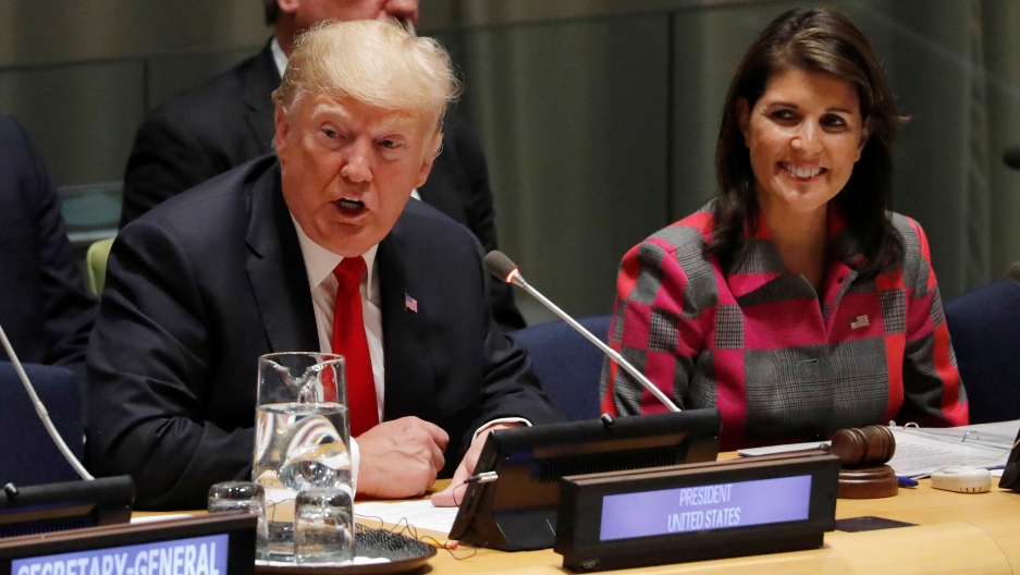 US President Donald Trump speaks as UN Ambassador Nikki Haley looks on