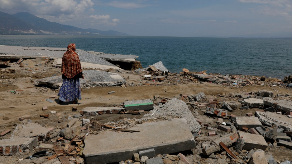 A woman wearing a head covering looks out on the ocean after a tsunami in Indonesia's Sulawesi Island..