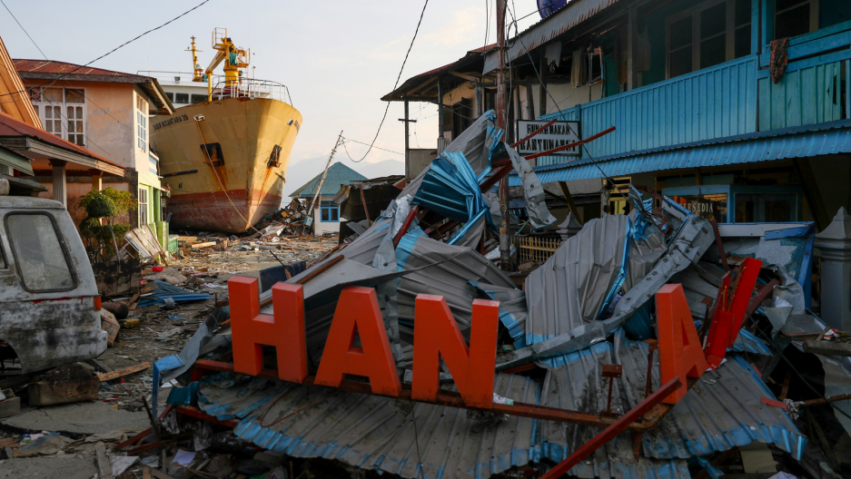 a ship and other debris on a beach in indonesia after a tsunami