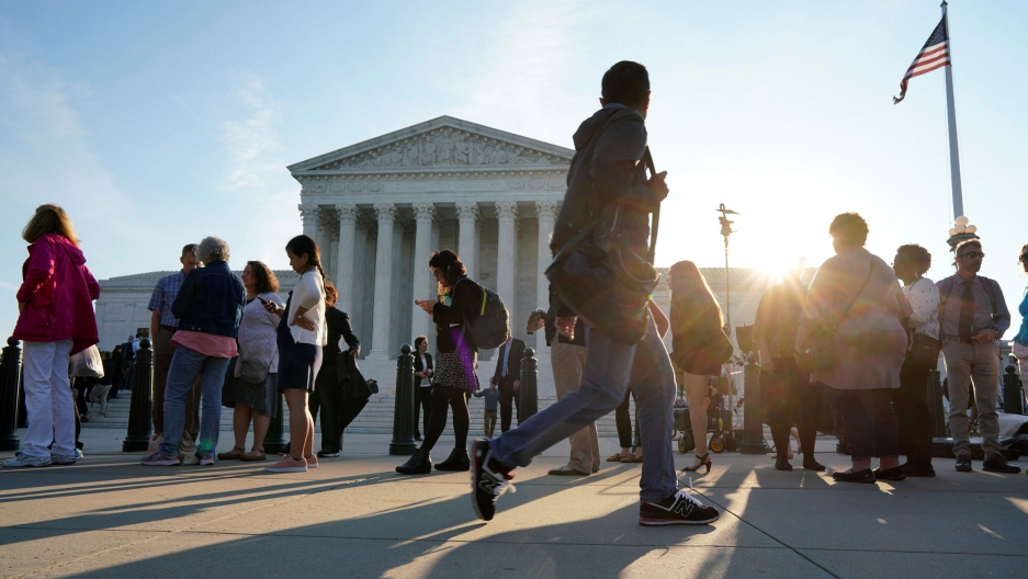 People are shown waiting in line with the Supreme Court in the background.