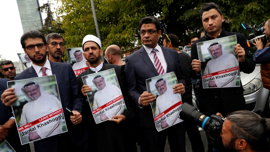 Four men wearing suits stand abreast holding posters of Saudi journalist Jamal Khashoggi's picture.
