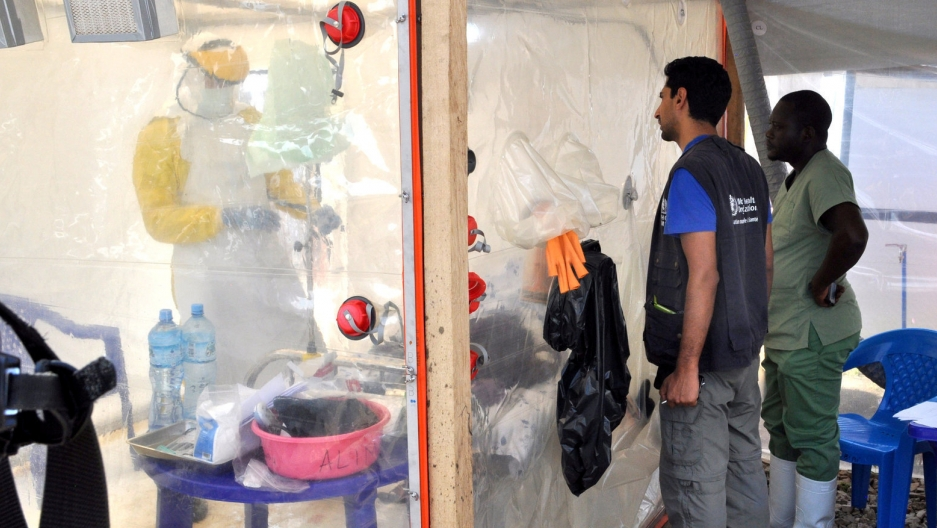 A doctor cares for a patient wearing protective clothing inside an isolate cube at a treatment center