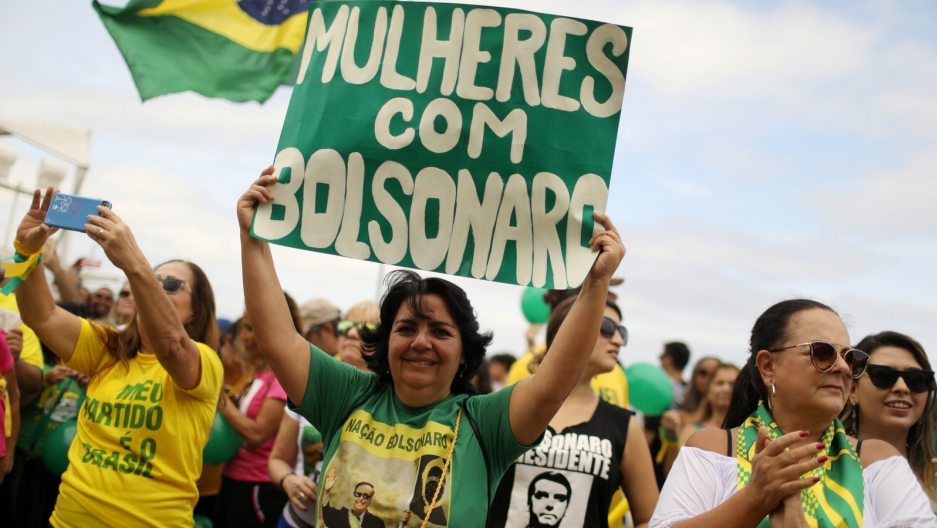 "A woman holds up a green sign with white letters that says ""Women for Bolsonaro"""