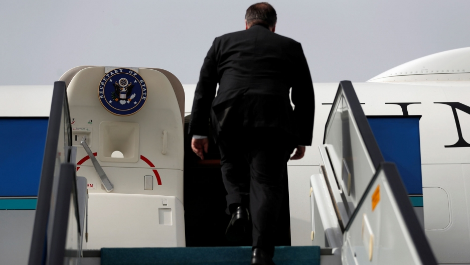 US Secretary of State Mike Pompeo is seen walking up the staircase leading to his plane emblazoned with the Secretary of State logo.
