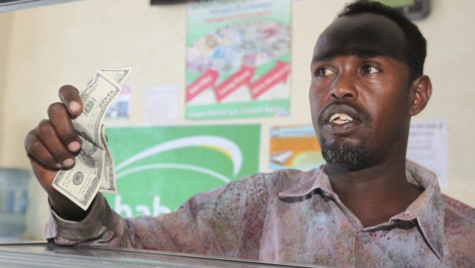 A customer receives US notes from a teller at the Dahabshill money transfer office in Mogadishu, Somalia, Feb. 16, 2015.