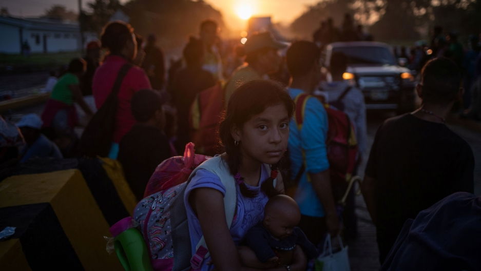 A girl traveling with other migrants is shown holding a doll and wearing a back-pack en route to the United States.
