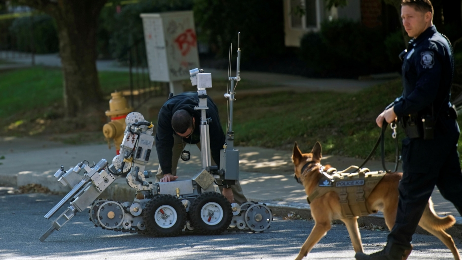 Law enforcement personnel walks with a dog while another bends over a bomb disposal robot.