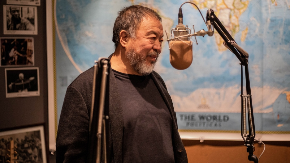 Chinese artist Ai Weiwei stands near a microphone in a radio studio.