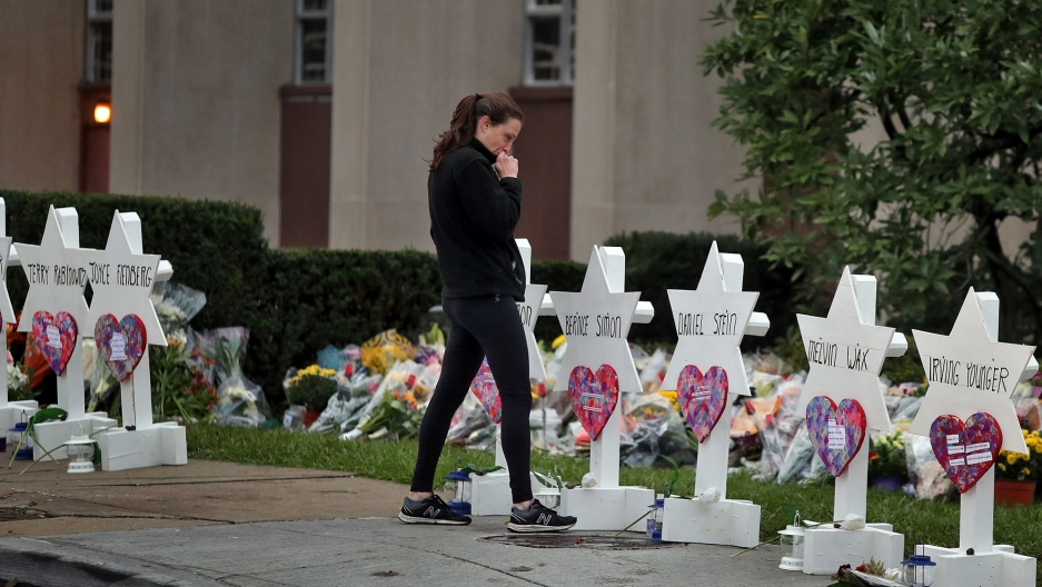 A woman is shown with her hand to her face standing at a makeshift memorial outside the Tree of Life synagogue.